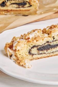 하얀 테이블에 흰 설탕 유약이 있는 맛있는 양귀비 씨 조각 케이크의 클로즈업 샷