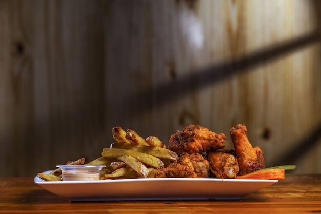 테이블에 감자 튀김과 함께 맛있는 매운 닭 다리의 근접 촬영 샷