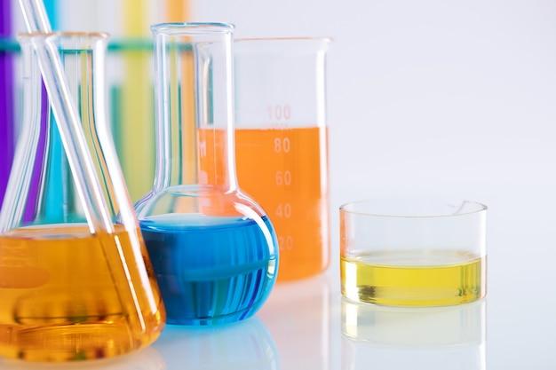 실험실의 흰색 표면에 다채로운 액체가 있는 다른 플라스크의 클로즈업 샷