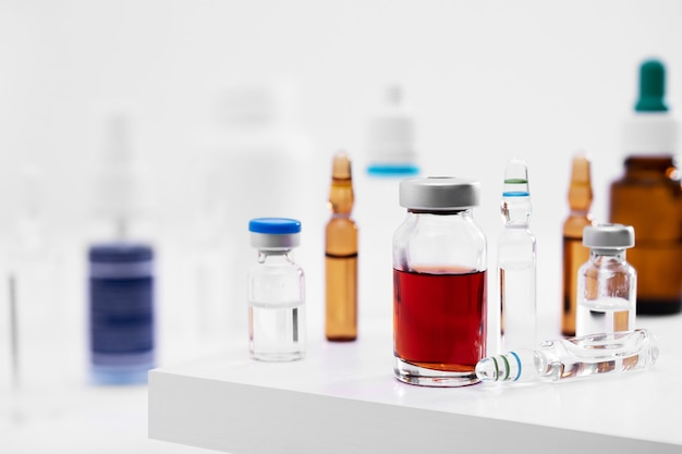 실험실의 흰색 표면에 액체가 있는 다른 유리 병의 근접 촬영