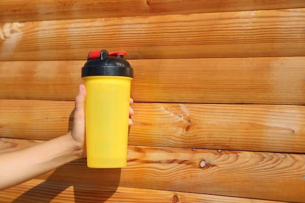 木の壁の近くに水筒を持っている女性の手のクローズアップショット。テキスト用のスペース