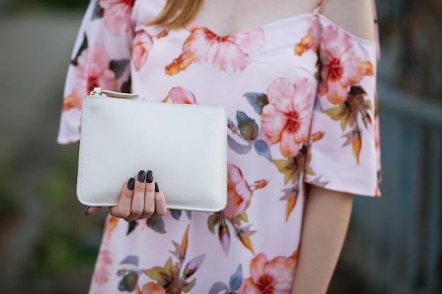 白い革の財布を持っている女性の手のクローズアップショット。テキスト用のスペース