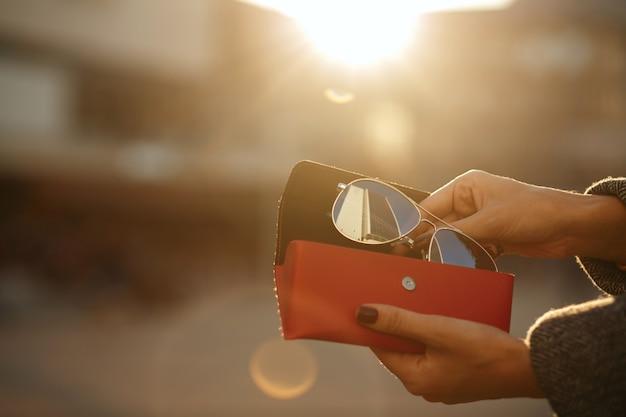 太陽の背景に赤い眼鏡ケースを開く女性の手のクローズアップショット。テキスト用のスペース