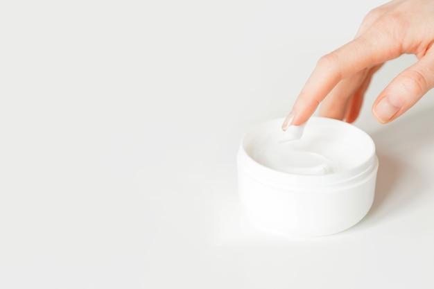 保湿クリームに触れる女性の手のクローズアップショット