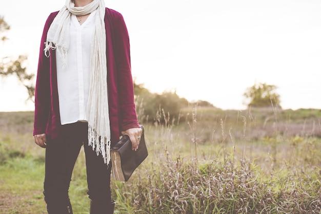 ぼやけた背景で聖書を保持しながら芝生のフィールドに立っている女性のクローズアップショット