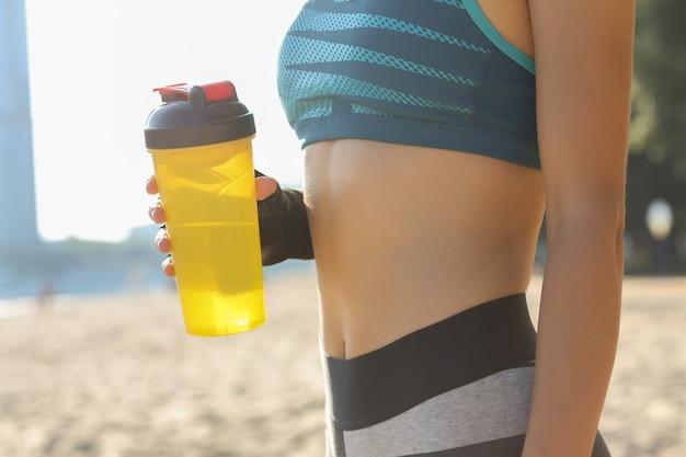 ビーチでポーズをとって水のボトルを保持しているスポーツフォームを持つフィットネス女性のクローズアップショット。テキスト用のスペース