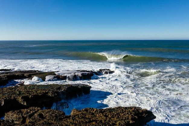 화창한 날 바위 해변을 치는 거품 파도의 근접 촬영
