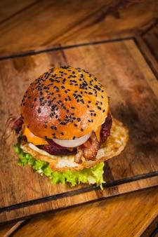Крупным планом выстрелил свежий вкусный гамбургер на деревянной поверхности