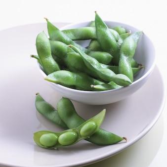 白いボウルとプレートテーブルの上に新鮮な緑の豆のクローズアップショット