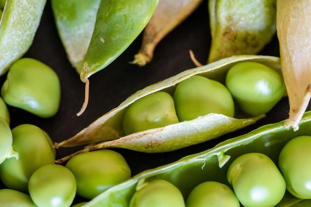 黒の木製の背景に新鮮な緑のエンドウ豆の種子のクローズアップショット