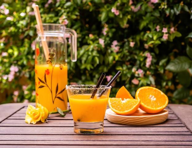 屋外の木製テーブルにオレンジのカットスライスと新鮮なオレンジジュースのクローズアップショット