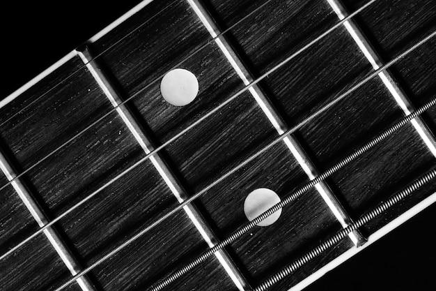 黒に分離されたアコースティックギターのフレットボードのクローズアップショット