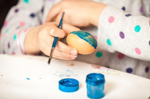 ブラシと絵のエステルの卵を持っている女の子のクローズ アップ ショット