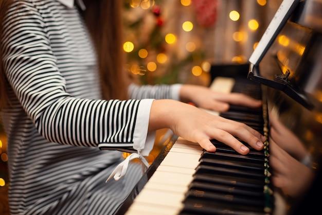 여자의 근접 촬영 샷 피아노의 키보드에 손