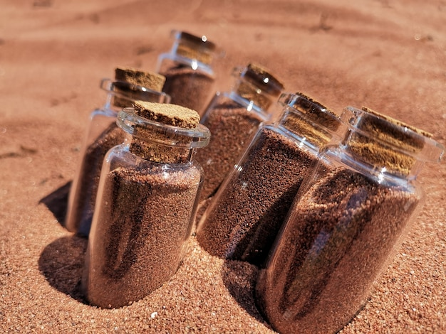 ビーチの砂の中に赤い砂で満たされたガラスの瓶のクローズアップショット