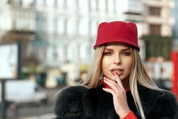 赤い帽子と毛皮のコートを着ているゴージャスなブロンドの女の子のクローズアップショット
