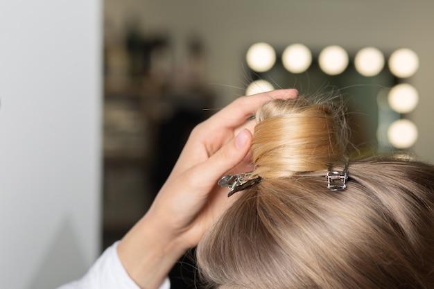 ビューティーサロンでスタイリングのために髪を準備している美容師の手のクローズアップショット