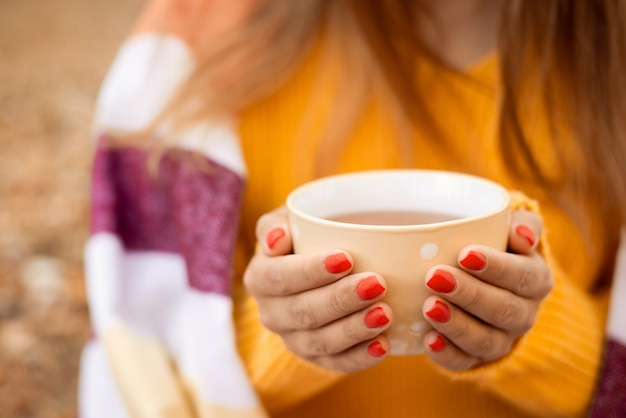 公園に座っている暖かいお茶のカップを保持している女の子の手のクローズアップショット