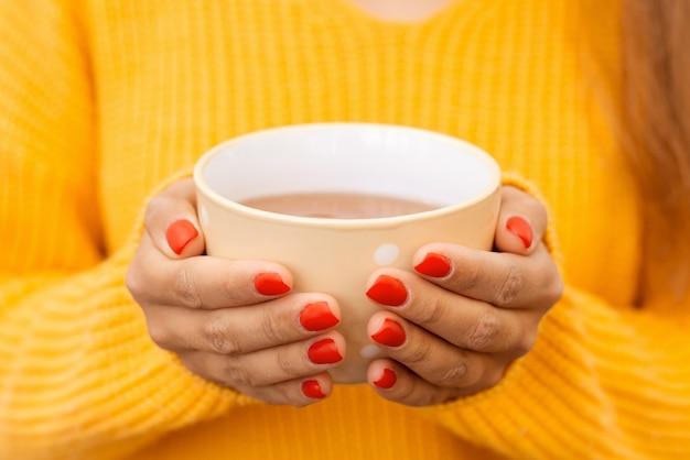 따뜻하고 맛있는 차 한 잔과 함께 한 소녀의 손을 클로즈업