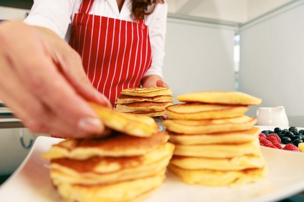 ぼやけた前景のスタックからパンを拾いながら赤いエプロンを着ているシェフの手で焼きたてのおいしいふわふわホットゴールデン良い香りのパンケーキスナックのヒープのクローズアップショット。