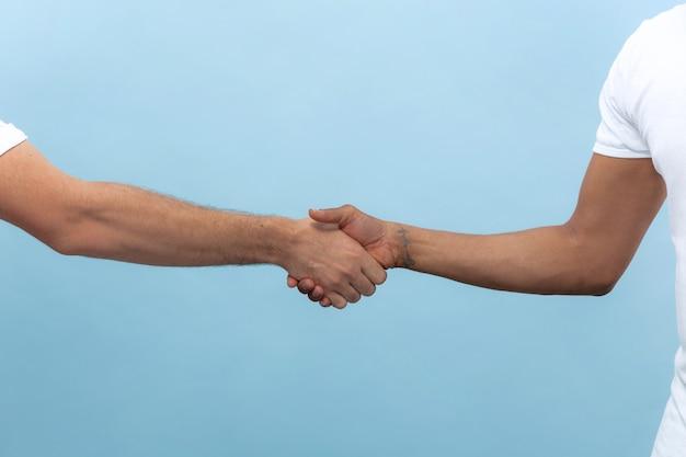 青い壁に分離された手を握って人間のクローズアップショット。人間関係、友情、パートナーシップ、ビジネスまたは家族の概念。コピースペース。