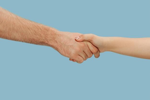 Снимок крупным планом человека, держащего руки, изолированного на синем