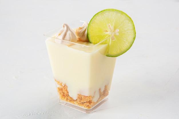 작은 머랭과 레몬 한 조각을 맨 위에 얹은 레몬 파이 디저트의 클로즈업 샷