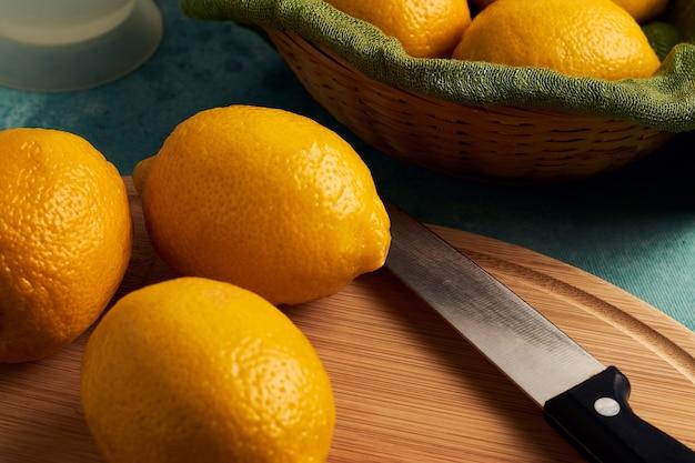 Снимок крупным планом лимонов на деревянной разделочной доске и в корзине