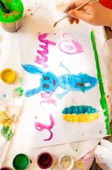 Снимок крупным планом маленькой девочки, рисующей синего кролика на холсте