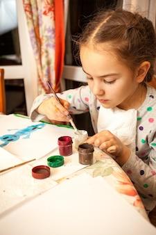 Снимок крупным планом маленькой девочки, рисующей акварелью