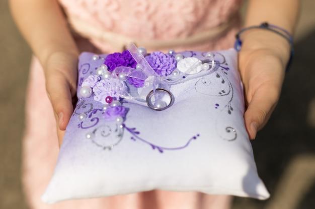 Снимок крупным планом маленькой девочки, держащей подушку с обручальными кольцами