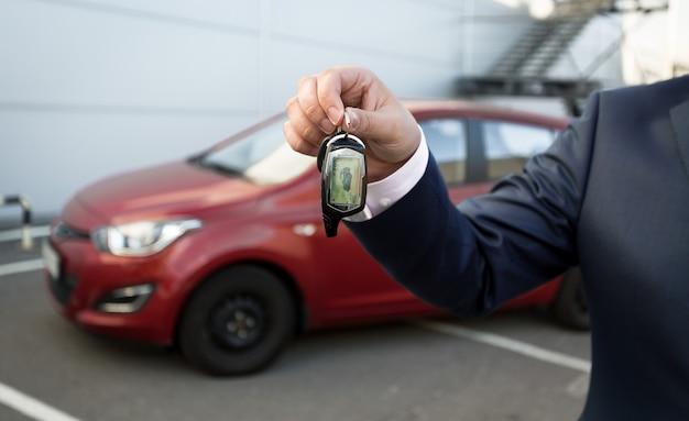 アラームリモコンで車のキーを示すスーツを着た男のクローズアップショット