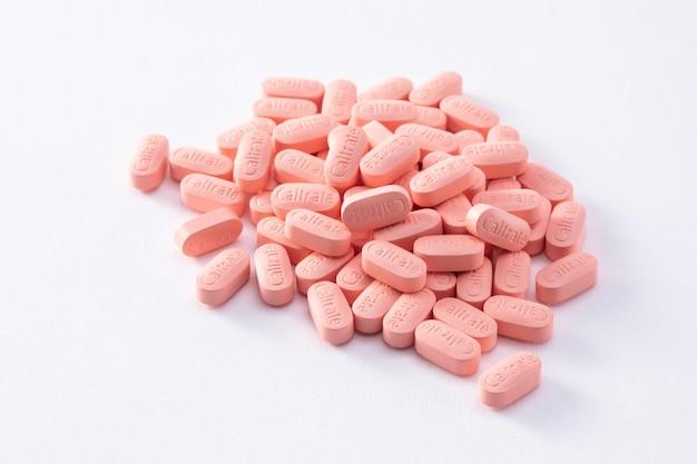 白い背景で隔離の多くのカルシウム錠剤のクローズアップショット