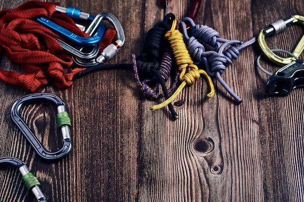 木製の表面に多くのカラフルな登山カラビナと結び目のクローズアップショット
