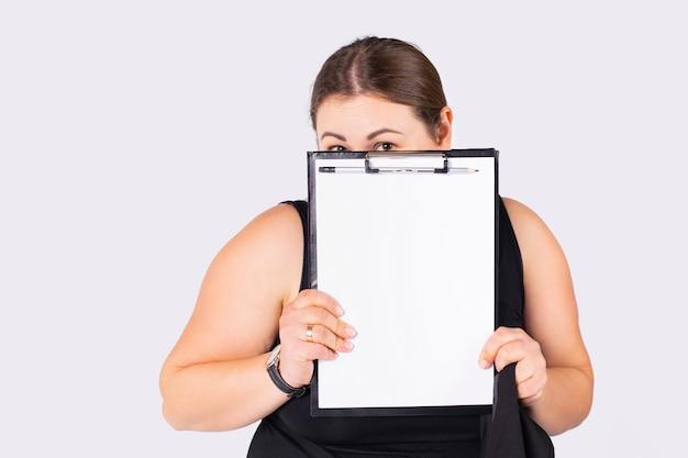 성숙한 여성 사업가의 클로즈업 샷과 의심스러운 얼굴 표정 회색 배경이 있는 빈 모의 흰색 시트가 있는 검정 클립보드를 엿보기