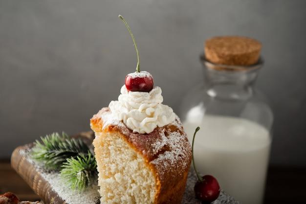 Крупным планом снимок молока, вкусного торта со сливками, сахарной пудрой и вишней на книгах
