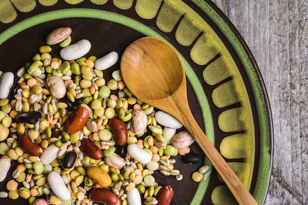 木のスプーンで皿に混合豆のクローズアップショット