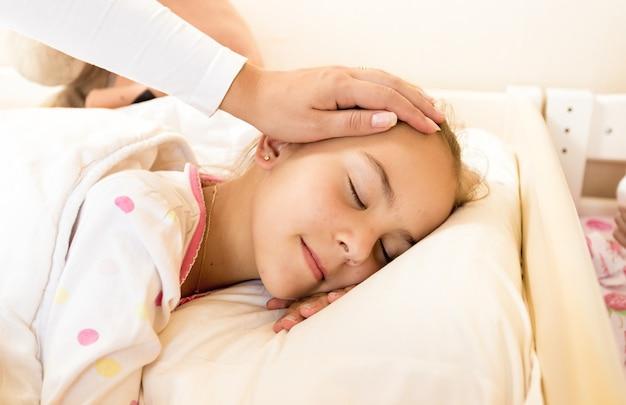 Снимок крупным планом матери, держащей руку на голове дочери в постели