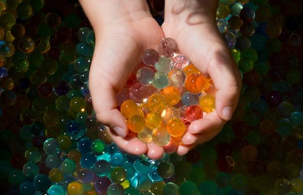 子供の小さな手で複数の色のボールorbisのクローズアップショット