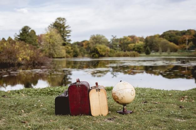ぼやけた水でデスクグローブの近くの芝生のフィールド上の古いスーツケースのクローズアップショット