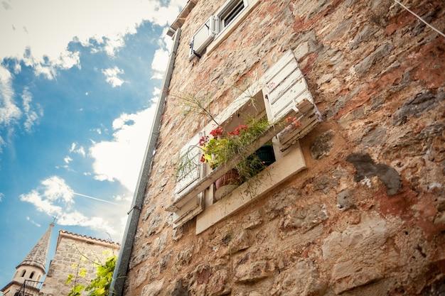 오래 된 석조 건물에서 화분으로 장식 된 열린 창의 근접 촬영 샷