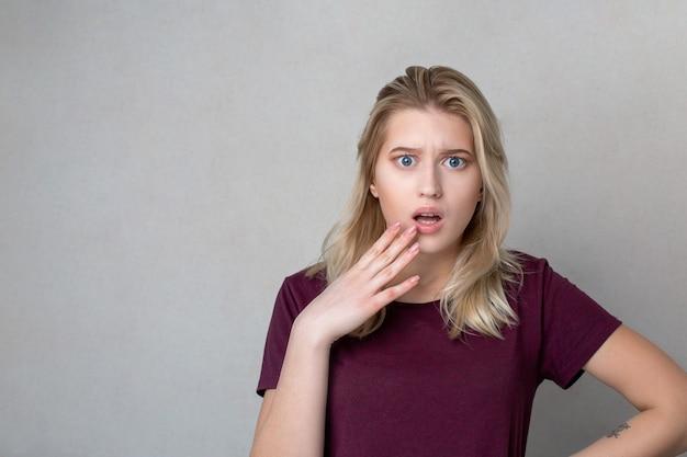 회색 벽 위에 서 있는 당황한 금발 소녀의 근접 촬영 샷. 텍스트를 위한 공간