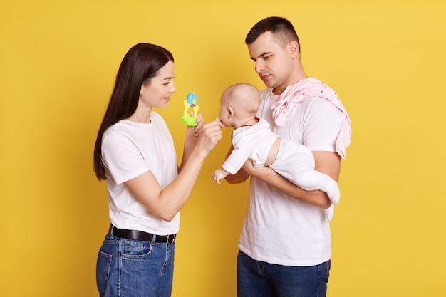 Снимок крупным планом: родители ласкают ребенка в руках отца и мама, стоящая рядом с ними, дает соску для ребенка и показывает игрушку новорожденному, семья в повседневной одежде и позирует у желтой стены.