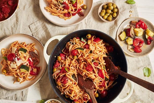 Макароны с овощами и ингредиентами на белом столе крупным планом