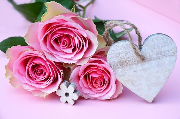 Крупным планом снимок розовых розовых цветов с деревянной биркой в виде сердца с пространством для текста