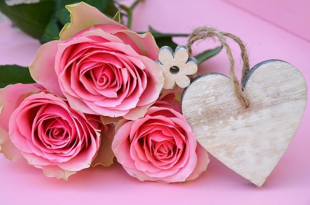 テキスト用のスペースとハートの木製タグとピンクのバラの花のクローズアップショット