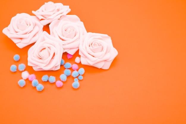 ピンクのバラとオレンジ色の背景に分離されたカラフルなポンポンのクローズアップショット