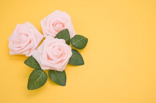 Крупным планом выстрел из розовых роз, изолированных на желтом фоне с копией пространства