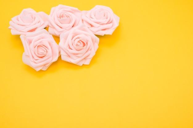 黄色の背景に分離されたピンクのバラのクローズアップショット 無料写真