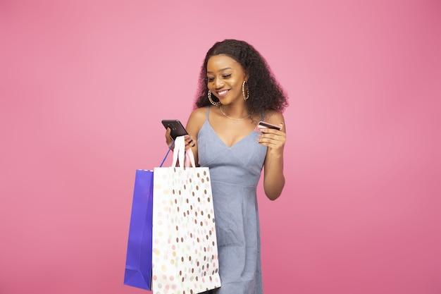 쇼핑백을 들고 행복함을 느끼는 예쁜 아프리카계 미국인 소녀의 클로즈업 샷
